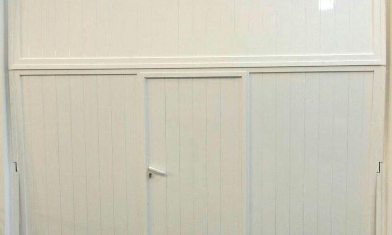 Portón de garaje blanco con puerta integrada